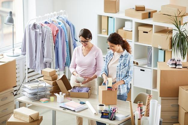 オフィスでクライアントのオンライン注文を梱包する2人の現代女性
