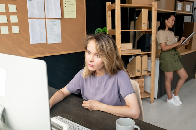 Две современные молодые работницы складского помещения проверяют и принимают онлайн-заказы клиентов, используя компьютер и тачпад