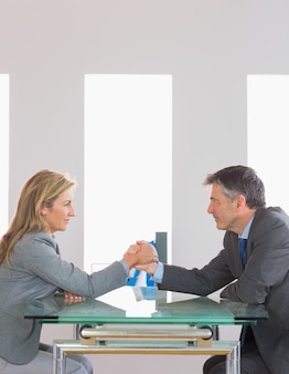 Two content businesspeople having an arm wrestling sitting around a table