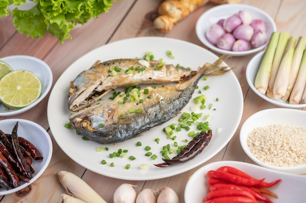Two cooked mackerel, placed in a white dish, sprinkled with spring onions.