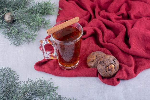 Due biscotti, un bastoncino di cannella e una tazza di tè su sfondo bianco.