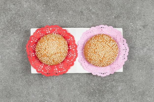 Due biscotti con semi di sesamo sul piattino bianco