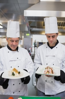 Two cooks proudly presenting their meals