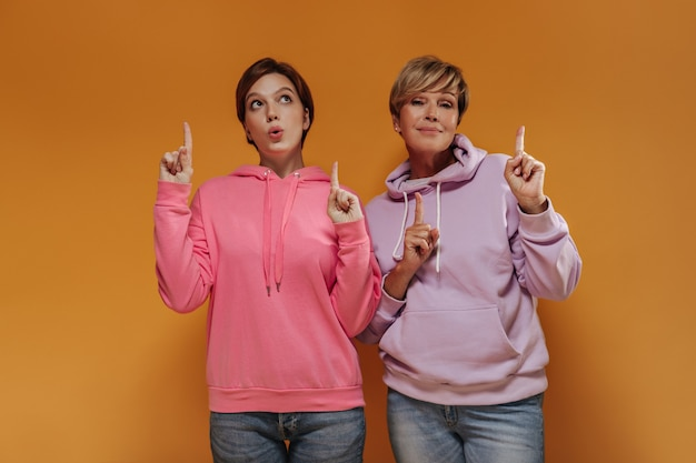 ピンクとライラックの広いパーカーとジーンズの短い髪の2人のクールな女性は、親指を立ててオレンジ色の背景でポーズをとっています。