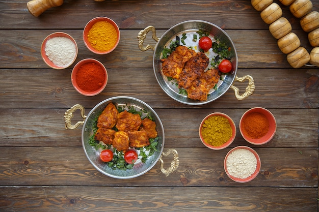 Two coppery pans with marinated chicken garnished with tomatoes and herbs