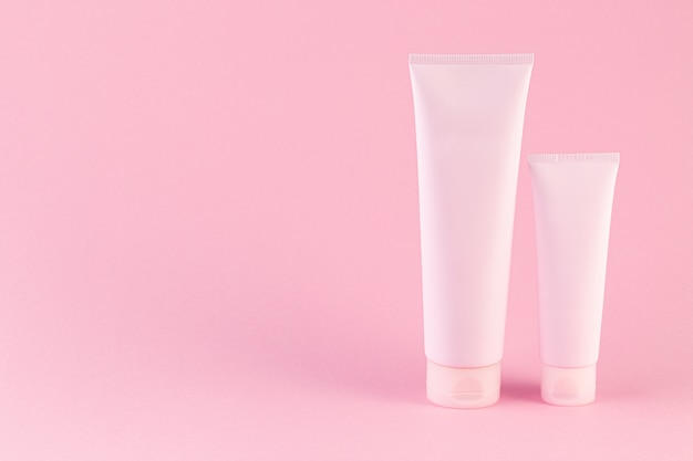 Two cosmetic tubes package on pastel pink background.