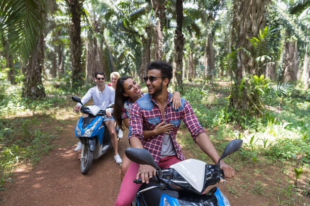 Two couple driving scooter in tropical forest cheerful friends enjoy road trip together
