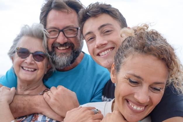 Две пары мать и сын разных поколений обнимаются и улыбаются на открытом воздухе счастливая семья вместе
