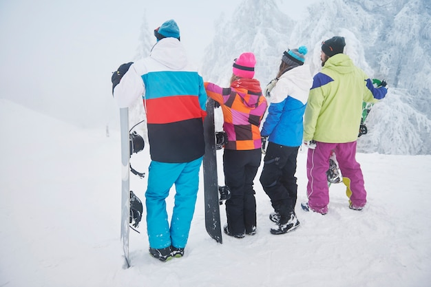 Due coppie che si divertono e fanno snowboard