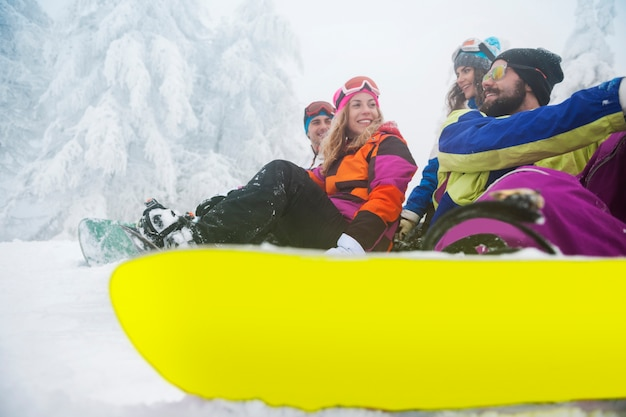 Two couples having fun and snowboarding