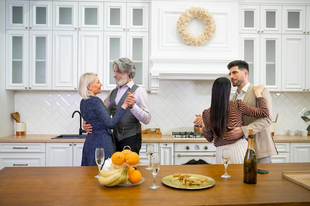 Two couples parents and young husband and wife dancing in light stylish kitchen at home party