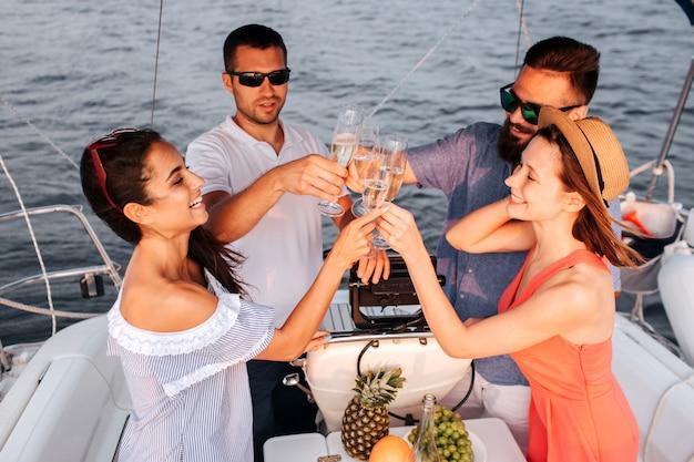 Две пары стоят друг перед другом и приветствуют бокалами шампанского. они смотрят на это и улыбаются. люди плывут на яхте.