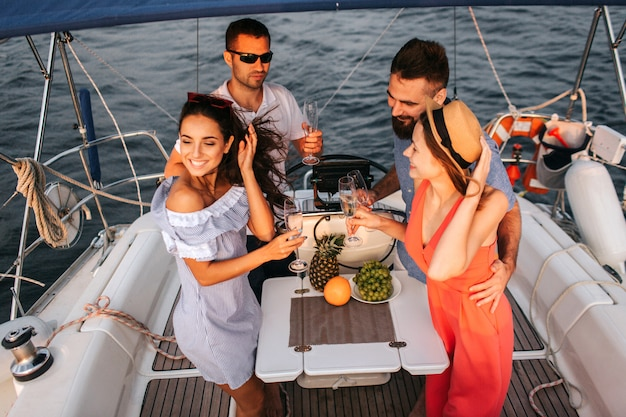 Two couples on yacht have party. they holds glases of champaigne. women are smiling. they look happy. men stand with them and embrace their girlfriends.