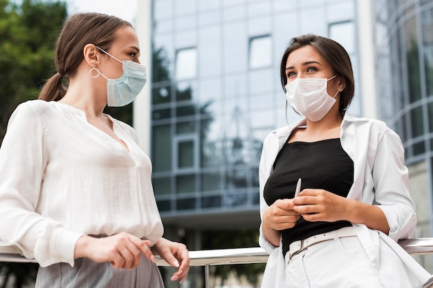 Two coworkers chatting outdoors during pandemic while wearing medical masks