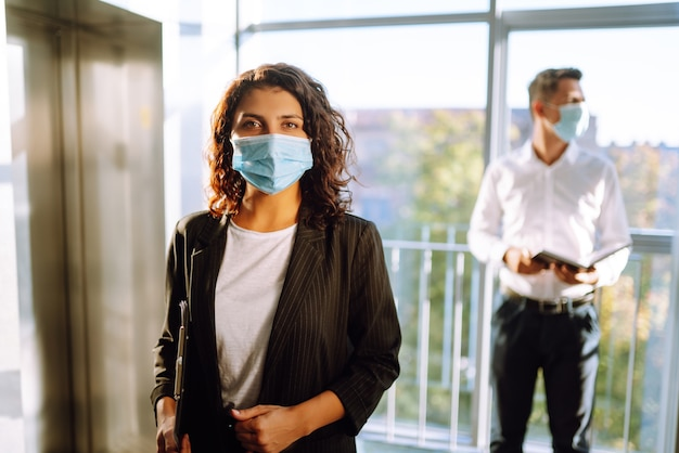 Two coworkers in protective face masks discussing project, sharing ideas.