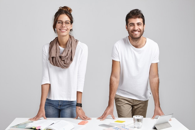 Two coworkers stand in modern office at table with documents and tablet