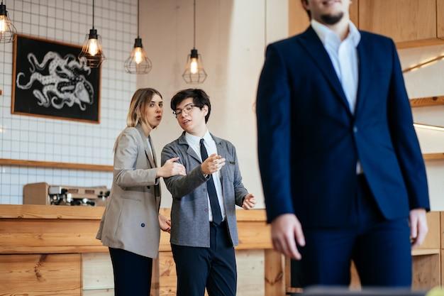 2人の同僚がオフィスで男性の同僚を見つめておしゃべり