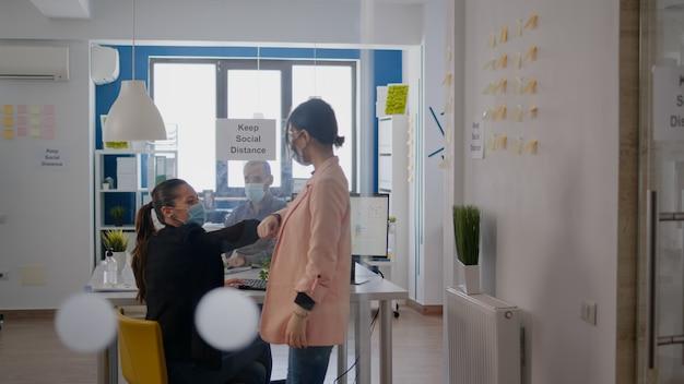 コロナウイルスの世界的大流行の際に、ウイルス病の感染を防ぐために医療用フェイスマスクを着用してビジネスプロジェクトで働いているときに、2人の同僚が肘に触れました。会社は社会的距離を維持します