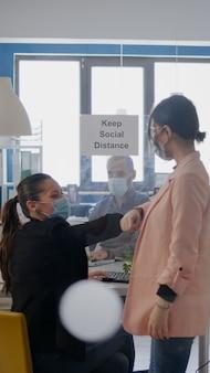 두 명의 동료가 코로나바이러스 전염병 동안 팔꿈치를 만지고 바이러스 질병 감염을 예방하기 위해 의료용 안면 마스크를 쓴 비즈니스 프로젝트에서 일하고 있습니다. 회사는 사회적 거리를 유지