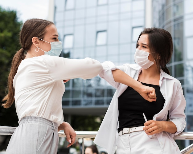 Two coworkers touching elbows outdoors during pandemic while wearing masks