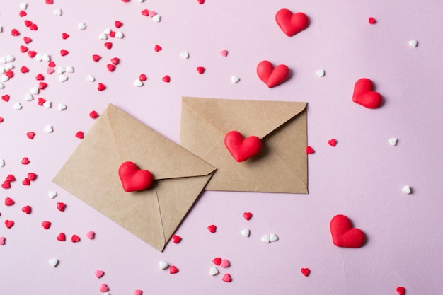 Two craft paper postal envelope with multicolor sweet sugar candy hearts. love message or gift concept.