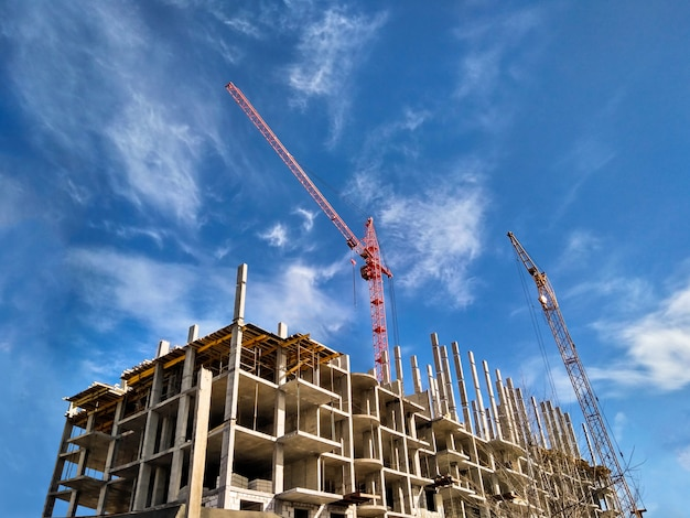 Two cranes building residential house at daylight blue sky background. construction concept