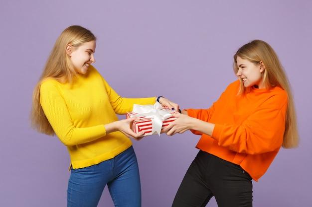 보라색 파란색 벽에 고립 된 선물 리본으로 빨간 줄무늬 선물 상자를 들고 생생한 옷에 두 미친 금발 쌍둥이 자매 여자. 사람들이 가족 생일, 휴가 개념.