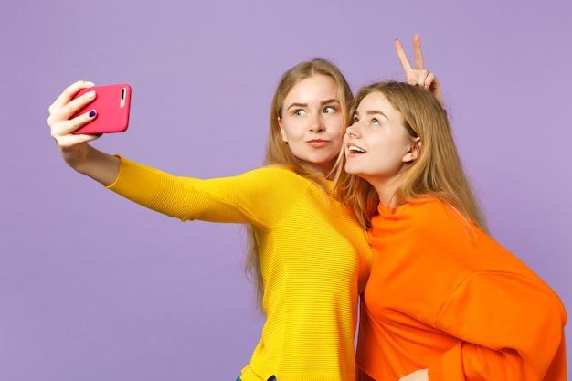 パステルバイオレットブルーの壁に隔離された携帯電話でselfieショットをしているカラフルな服を着た2人のクレイジーな若いブロンドの双子の姉妹の女の子。人々の家族のライフスタイルの概念。