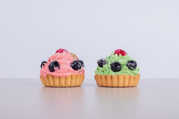 Two creamy cupcakes on white.