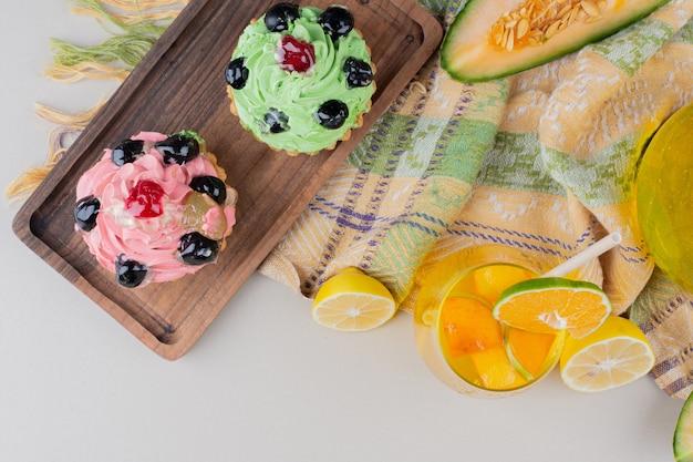 Due cupcakes cremosi sulla tavola di legno.