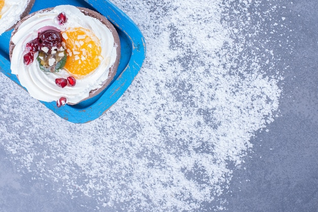 青い板に砂糖粉が入った2つのクリーミーなペストリー