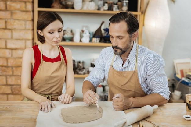 2人の創造的な陶芸家。仕事の過程で素晴らしいアイデアを持ちながら思慮深く感じている2人の創造的な熟練した陶芸家 Premium写真