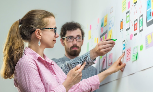 Two creative designers develop mobile applications in the workplace.