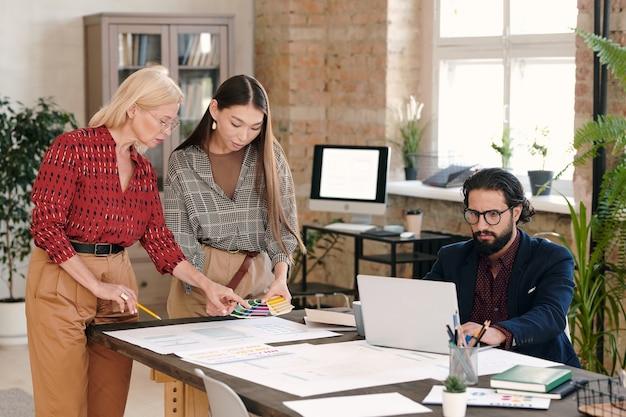 Две креативные женщины-дизайнеры выбирают цвет для нового мобильного приложения, а их молодая коллега с ноутбуком ищет данные в интернете