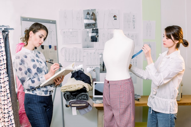 Two creative female seamstresses working in stylish atelier. woman seamstress measuring mannequin, holding tape, while other woman fashion designer working with sketches for new clothes
