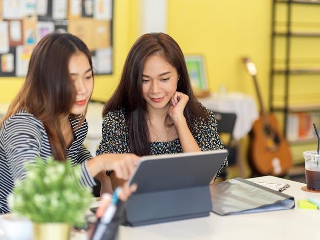 두 명의 창의적인 밀레니얼 여성 비즈니스 스타트업 소유자가 비즈니스 모델에 대해 이야기하고 계획합니다.