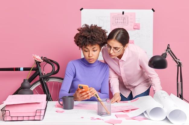 スマートフォンの画面に集中している2人のクリエイティブな女性の同僚が、デスクトップでプロジェクトのポーズをとるのに必要な情報を、周りの紙で真剣に表現しています。人々はコラボレーションを行います