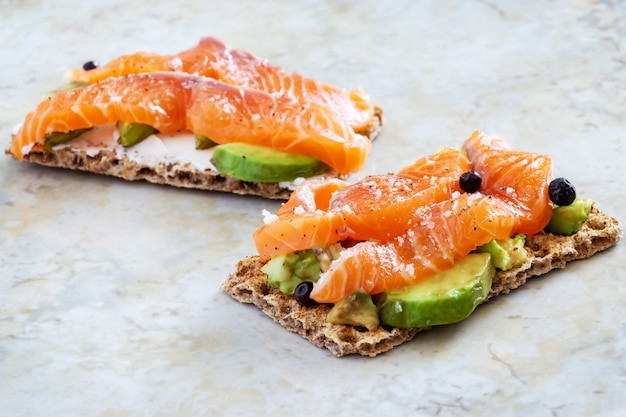 Two crisp sandwiches with avocado and smoked salmon.