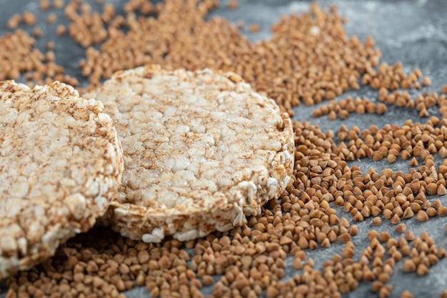 Due fette biscottate e grano saraceno crudo sulla superficie di marmo