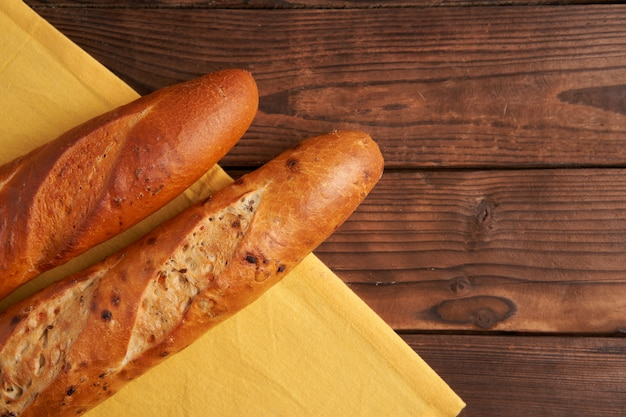 Two crispy french baguettes lie on an old wooden table