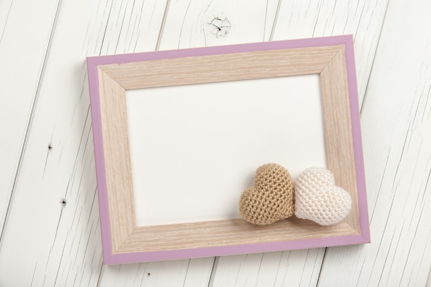 Two crochet hearts and blank wooden frame