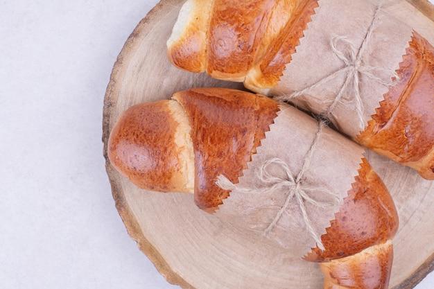 Due panini croissant in involucro di carta su tavola di legno.