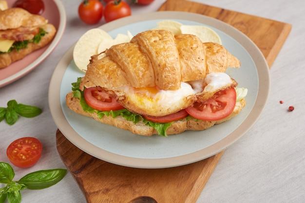 Два бутерброда с круассаном на деревянном столе, вид сверху