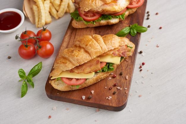 Два бутерброда с круассаном на деревянном столе
