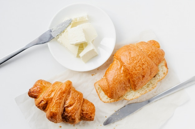 Two croissants and butter on white table, top view.