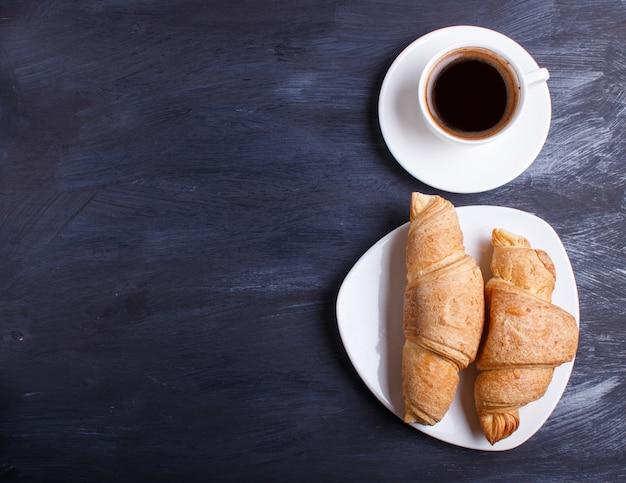 Two croissants with cup of coffee on white plate on black wooden background