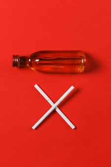 Two crossed white cigarettes like letter x, bottle with alcohol cognac, whiskey on red background