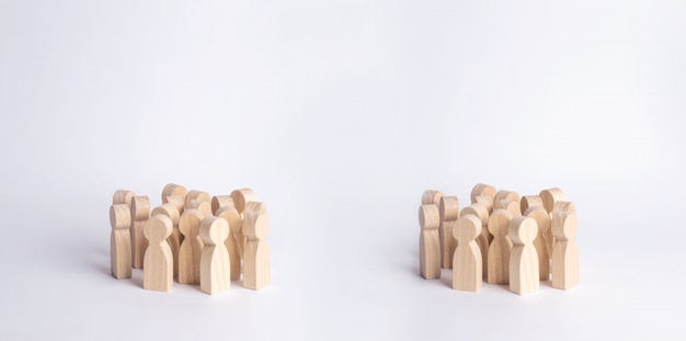 Two crowds of wooden figures of people are standing on a white background.