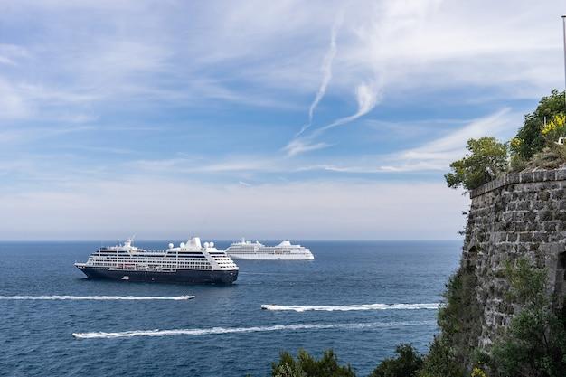 たくさんのパワーボートに囲まれた晴れた日の海での2隻のクルーズ船。