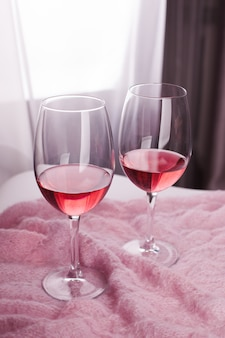 Two crystal glasses of pink wine on abstract